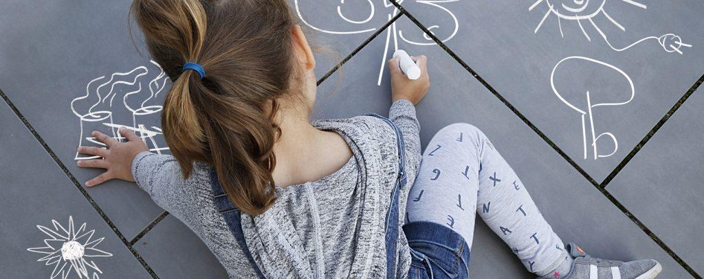 Kind malt Lausitzer Kraftwerk und Sonne mit Kreide